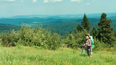 Kleines-Wanderermädchen-Mit-Reiserucksack-Auf-Gebirgshintergrundkindlächeln