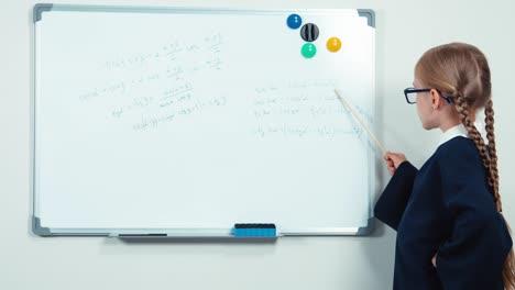 Little-Student-Holding-Pointer-Standing-Near-Whiteboard