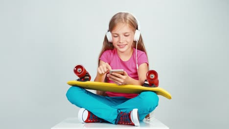 Portrait-7-8-Years-Schoolgirl-Listening-Music-In-Headphones-Holds-Cell-Phone