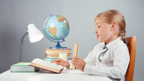 Portrait-Blonde-School-Girl-7-8-Years-Reading-Book-And-Eating-Wafer