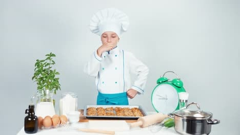 Portrait-Chef-Cook-Girl-Child-7-8-Years-Old-Eating-Biscuit-And-Smiling-At-Camera