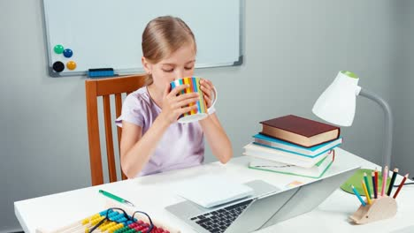 Portrait-Child-7-8-Years-Looking-At-Laptop-And-Holding-Cup-Of-Tea