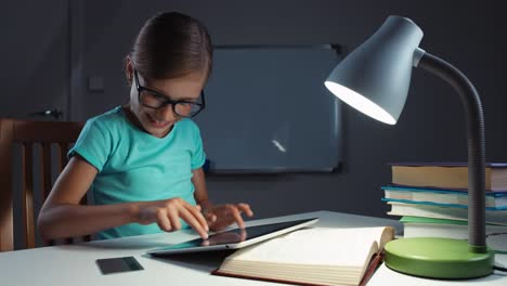 Girl-7-or-8-years-old-uses-credit-card-and-a-tablet-at-night-