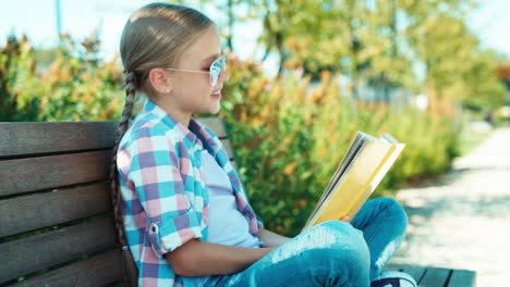 Portrait-Child-7-8-Years-Reading-Book-In-Sunglasses-On-The-Bench-And-Smiling