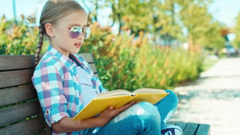 Portrait-Child-7-8-Years-Reading-Book-On-The-Bench-Panning