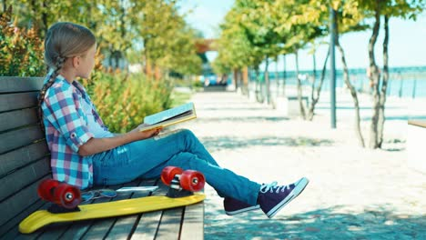 Portrait-Child-7-8-Years-Reading-Book-Sitting-On-The-Bench-And-Looking-At-Camera
