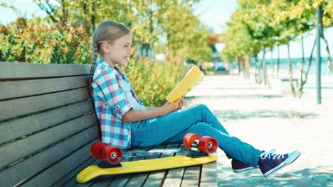 Portrait-Child-7-8-Years-Reading-Book-Sitting-On-The-Bench-And-Smiling-At-Camera
