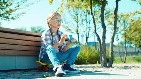Portrait-Child-Girl-7-8-Years-Blowing-Bubbles-And-Sitting-On-Skateboard