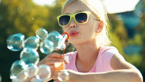 Portrait-Child-Girl-7-8-Years-In-Sunglasses-Blowing-Soap-Bubbles-On-Fountain