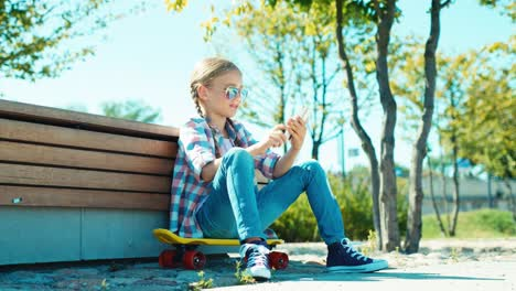 Portrait-Child-Girl-7-8-Years-Sitting-On-Skateboard-And-Using-Smartphone-Typing