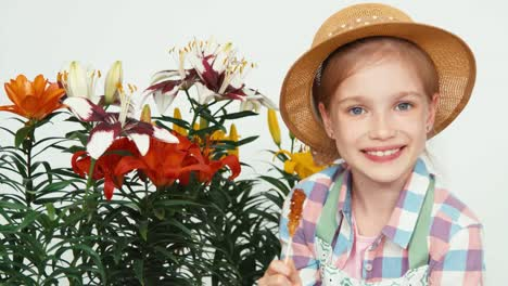 Portrait-Cute-Flowergirl-Child-In-Hat-Sitting-Near-Flowers-And-Eating-Lollipop