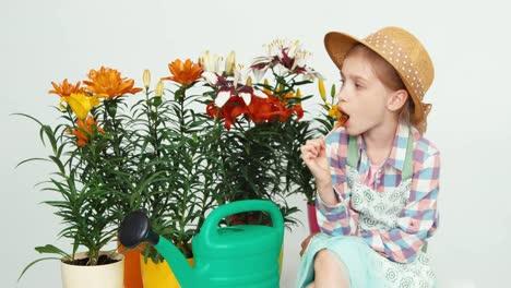 Portrait-Cute-Flowergirl-Child-Sitting-Near-Flowers-And-Eating-Lollipop