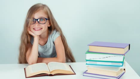 Portrait-Cute-Student-Girl-7-8-Years-In-Glasses-Reading-Book-And-Smiling