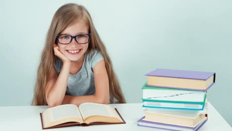 Portrait-Cute-Student-Girl-7-8-Years-Reading-Book-And-Smiling-At-The-Camera