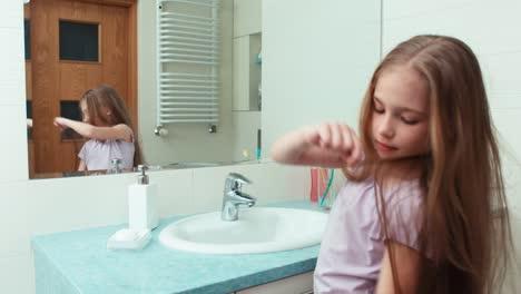 Retrato-Niña-De-7-Años-Acicalarse-El-Pelo-Largo-Ante-El-Espejo-En-El-Baño-