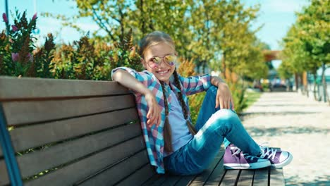 Portrait-Girl-7-8-Years-Laughing-Sitting-On-Bench-In-The-Park-And-Smiling