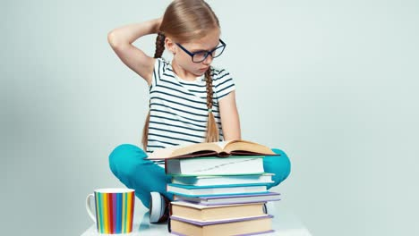 Portrait-Girl-7-8-Years-Old-In-Glasses-Reading-Book-And-Smiling-At-Camera