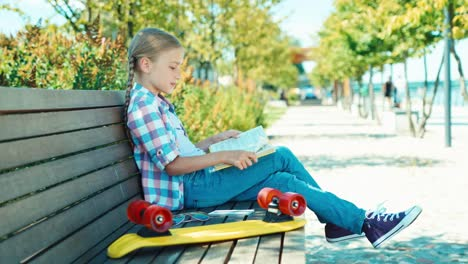 Portrait-Girl-7-8-Years-Reading-Book-And-Sitting-On-Bench-In-The-Park-Smiling