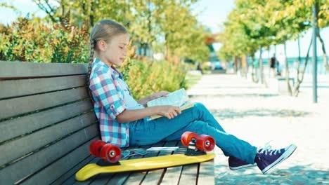 Retrato-Niña-7-8-Años-Leyendo-Un-Libro-Y-Sentado-En-Un-Banco-En-El-Parque-Sonriendo