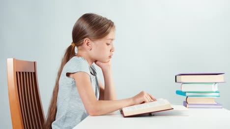 Portrait-Girl-Child-7-8-Years-Old-Reading-Textbook-And-Smiling-At-Camera