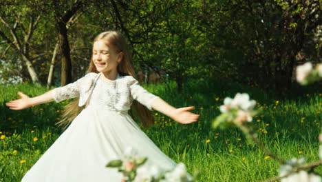 Young-girl-spinning-in-a-white-dress-in-the-park-near-a-blooming-tree