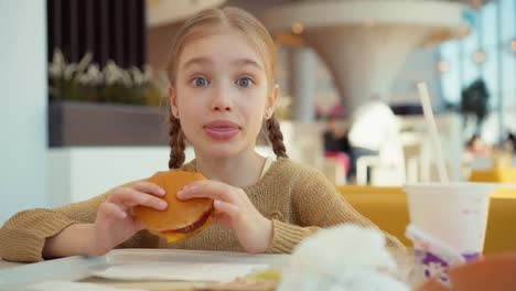 Portrait-girl-eating-burger-in-the-fast-food-and-smiling-at-camera
