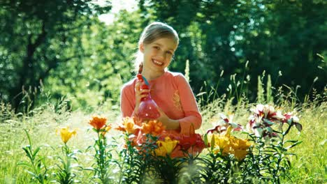 Portrait-Girl-Sprinkler-Her-Flowers-In-The-Garden-And-Smiling-At-Camera
