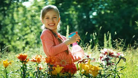 Portrait-Girl-Sprinkling-At-Camera-Near-Her-Flowers-In-The-Garden-Thumb-Up-Ok
