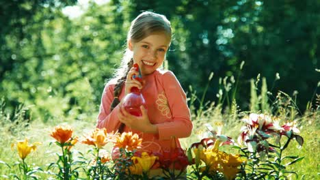 Portrait-Girl-Sprinkling-Her-Flowers-In-The-Garden-And-Laughing-At-Camera