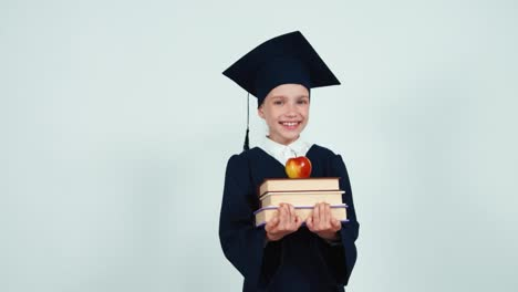 Portrait-Graduate-Girl-7-8-Years-In-The-Mantle-And-Hat-Holding-Books-And-Apple