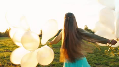 Happy-girl-runs-across-field-and-spinning-with-white-balloons-at-sunset