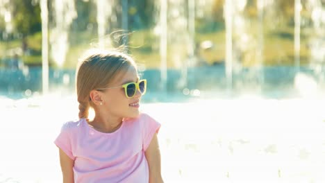 Portrait-Happy-Girl-Child-7-8-Years-Relaxing-Near-Fountain