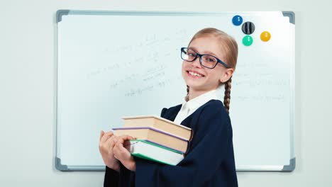 Portrait-Happy-Little-Student-Holding-Her-Books-And-Smiling-At-Camera