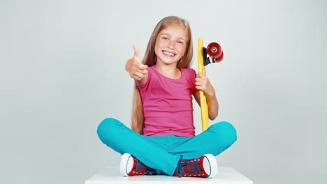 Portrait-Happy-School-Girl-Holds-Penny-Skateboard-And-Sitting-On-The-Floor
