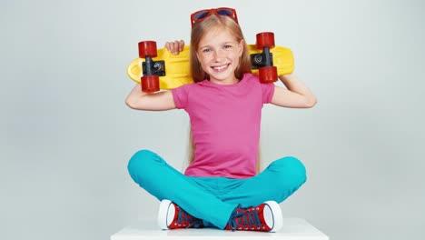 Portrait-Happy-School-Girl-Holds-Penny-Skateboard-On-White-Background