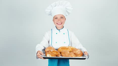 Portrait-Little-Baker-Holds-Oventray-With-Many-Breads-And-Smiling-At-Camera