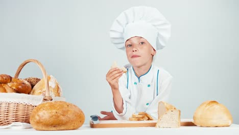 Portrait-Little-Baker-Near-Her-Basket-Eating-Slice-Of-Bread-Isolated-On-White