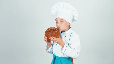 Portrait-Little-Baker-Sniffing-Black-Bread-And-Holds-It-In-Her-Hands-And-Smiling