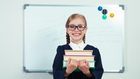 Portrait-Little-Student-Holding-Her-Books-And-Smiling-At-Camera-With-Teeth