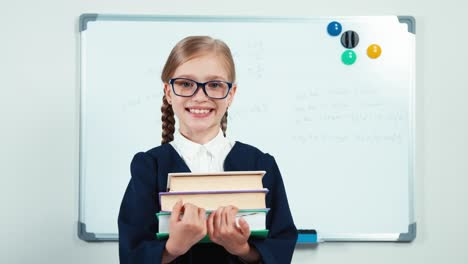 Portrait-Little-Student-Turns-At-Camera-Holding-Books-And-Smiling-With-Teeth