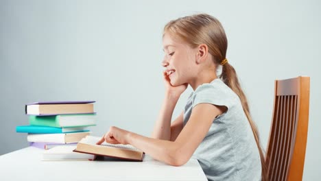 Portrait-Profile-Girl-Child-7-8-Years-Old-Reading-Textbook-And-Looking-At-Camera