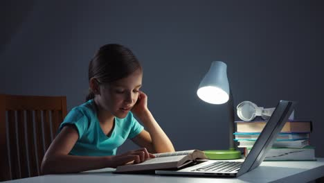 Portrait-School-Girl-7-8-Years-Old-Reading-Textbook-In-Her-Desk-In-The-Night