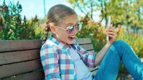 Niña-De-La-Escuela-De-Retratos-7-8-Años-Con-Teléfono-Inteligente-Y-Riéndose-De-La-Cámara
