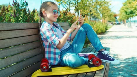 Portrait-School-Girl-7-8-Years-Using-Smartphone-Sitting-On-The-Bench-In-Park