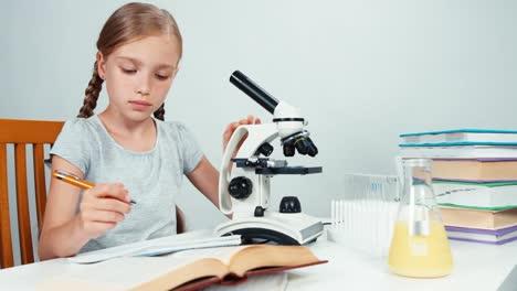 Niña-De-La-Escuela-De-Retrato-Con-Microscopio-Y-Algo-Escrito-En-Su-Cuaderno