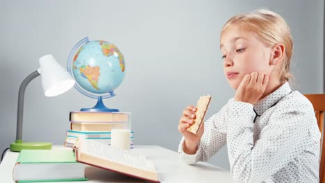 Portrait-Schoolgirl-7-8-Years-Eating-Sweet-Wafer-And-Reading-Book-At-The-Table