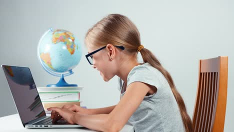Portrait-Schoolgirl-Foureyes-Typing-In-Her-Laptop-Sitting-At-Desk-Isolated