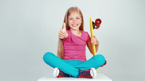 Portrait-Schoolgirl-Holds-Penny-Skateboard-And-Sitting-On-Floor-Thumb-Up-Ok