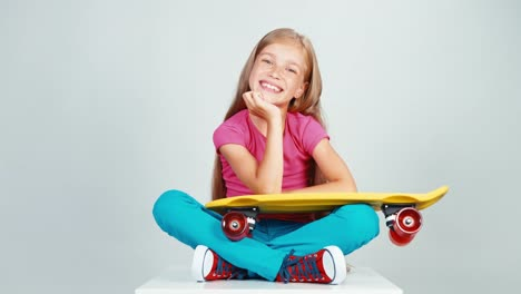 Portrait-Schoolgirl-Looking-At-Penny-Skateboard-And-Sitting-On-The-Floor