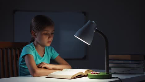 Portrait-Schoolgirl-Reading-A-Book-At-Night-In-The-Dark-And-Smiling